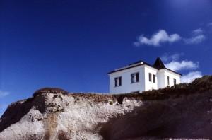Wyraźnie oddzielone niebo, skała i dom.